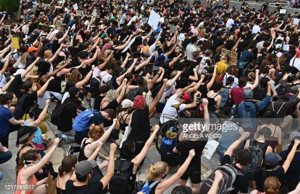 TOPSHOT Protesters take a knee and raise their fists during a Black Lives Matter demonstration in front of the Brooklyn Library and Grand Army Plaza...