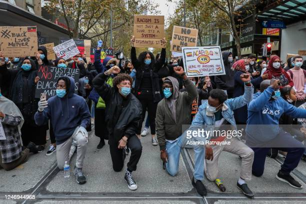 Protesters take a knee as they protest in Solidarity with clenched fists on June 06, 2020 in Melbourne, Australia. Events across Australia have been...