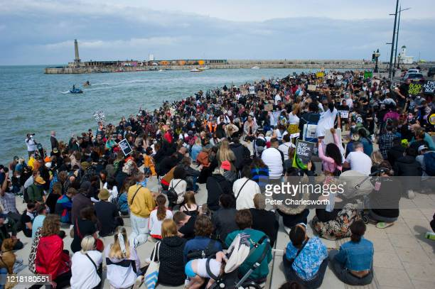 Protesters take a knee on the harbour steps Hundreds of local people joined a Black Lives Matter march along the coast of one of Englands oldest...