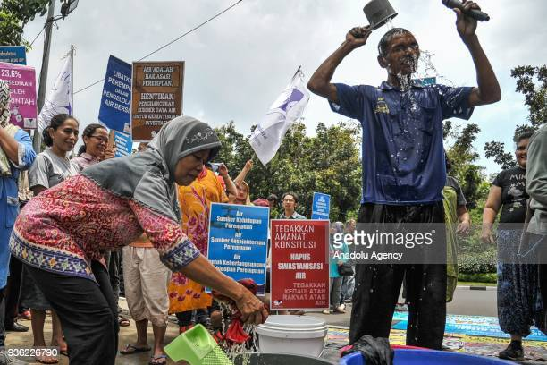 Protesters take bath and wash their clothes in front of the City Hall in Jakarta Indonesia on March 22 2018 This action was held to commemorate World...