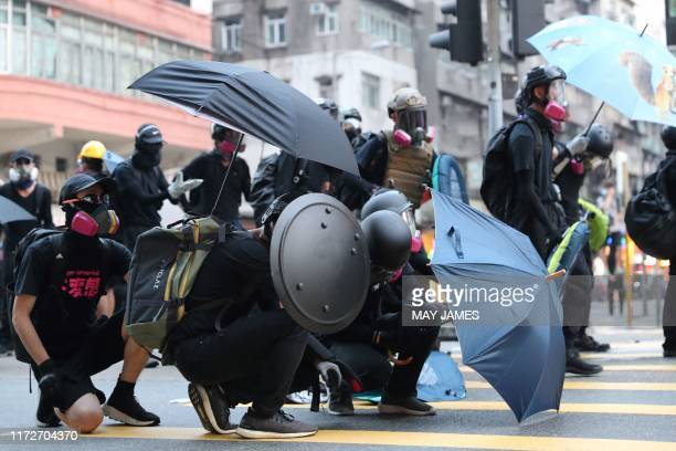 Protesters take cover as they stand off with police during a demonstration in the Sham Shui Po area in Hong Kong on October 1 as the city observes...