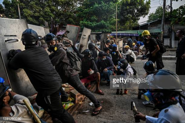 Protesters take cover behind homemade shields as they confront the police during a crackdown on demonstrations against the military coup in Yangon on...