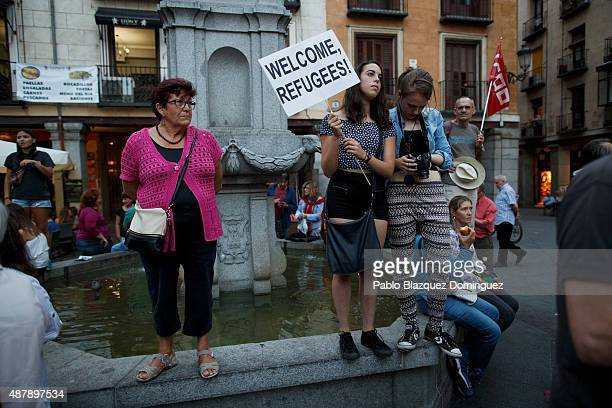 Protesters take part in a demonstration as one holds a placard reading 'Welcome refugees' during a demonstration to show solidarity and support for...