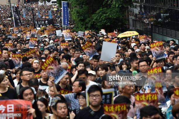 Protesters take part in a march to the West Kowloon railway station during a demonstration against a proposed extradition bill in Hong Kong on July 7...