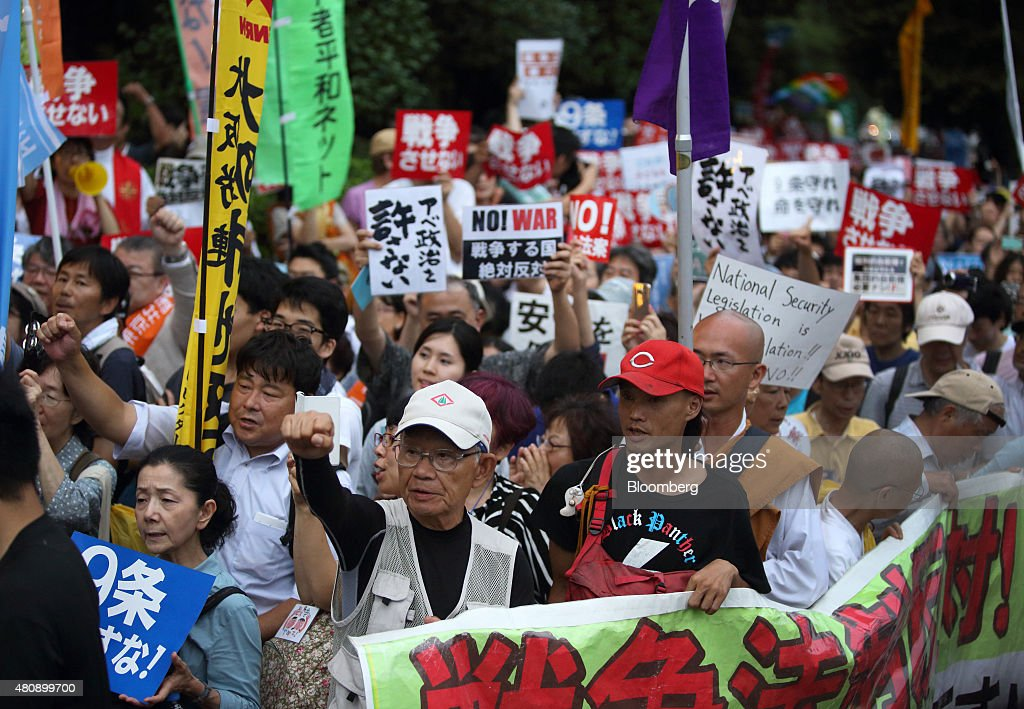 Protesters take part in a rally against the security bills outside the National Diet building in Tokyo, Japan, on Thursday, July 16, 2015. Japanese Prime Minister Shinzo Abe's security bills passed parliament's lower house Thursday after a night of noisy protests, as his push to expand the role of the military risks further eroding his public support. Photographer: Tomohiro Ohsumi/Bloomberg via Getty Images