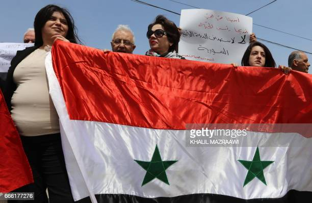 Protesters take part in a rally in front of the Syrian embassy in the Jordanian capital Amman on April 8 to show their support to the Syrian...