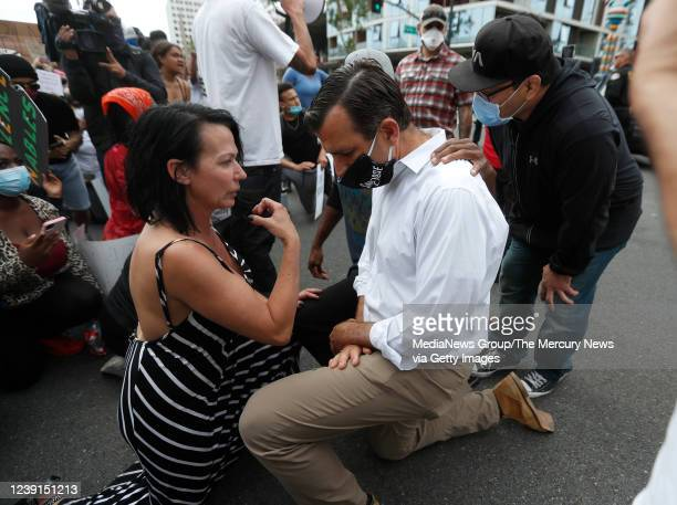 Protesters talk with San Jose Mayor Sam Liccardo as he takes a knee during a protest of the killing of George Floyd outside of San Jose City Hall in...