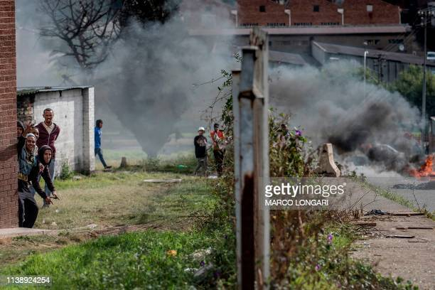 Protesters taunt South African police officers as they hide behind a wall in the street of Johannesburg on April 23 2019 during a protest against the...