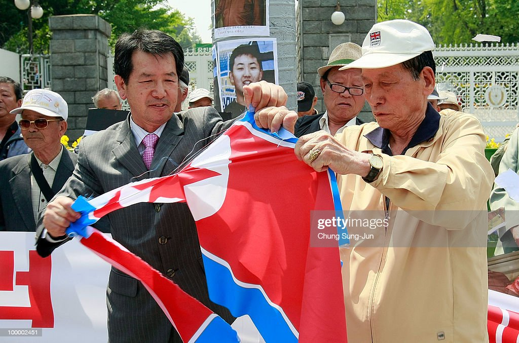 Protesters tear a North Korean national flag while protesting against North Korea on May 20, 2010 in Seoul, South Korea. The multinational investigation team concluded that North Korea's torpedo sank the South Korean warship on March 26, killing 46 sailors.