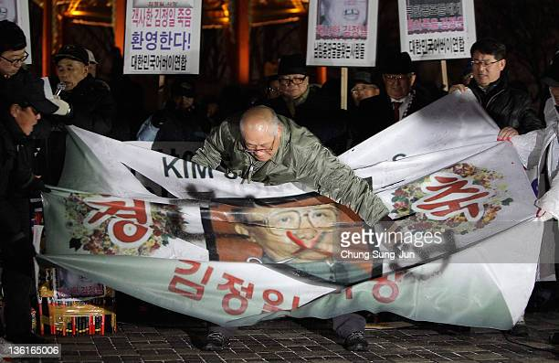 Protesters tear a portrait of late North Korean leader Kim Jong-Il during a rally to celebrate the death of North Korea's leader Kim Jong-Il on...