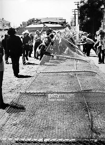 Protesters tear down the fence that was built by California Highway Patrol and Berkeley police officers when they destroyed trees flowers and plants...