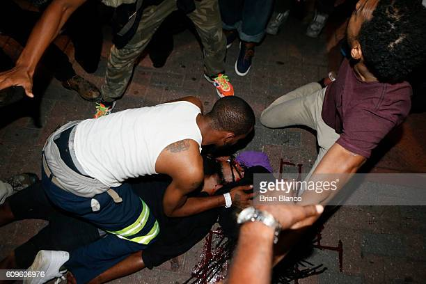 Protesters tend to a seriously wounded protester in the parking area of the the Omni Hotel during a march to protest the death of Keith Scott...