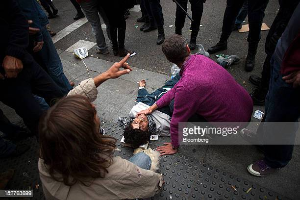 Protesters tend to an injured man during a demonstration against the government's austerity measures in the city centre of Madrid Spain on Tuesday...