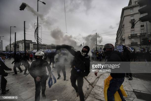 Protesters throw a smoke grenade back to riot police in Athens on January 20 2019 during a demonstration against the agreement with Skopje to rename...