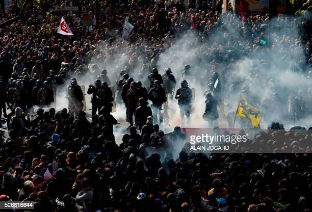 Protesters throw a smoke grenades towards French anti riot police during a clash during the traditional May Day demonstration in Paris on May 1 2016...