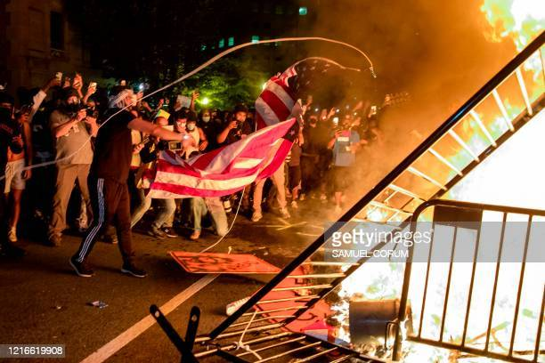 Protesters throw a US flag into a fire during a demonstration outside the White House over the death of George Floyd at the hands of Minneapolis...