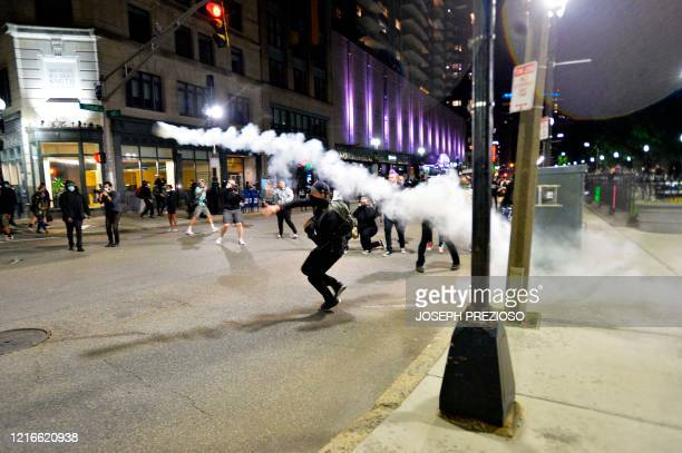 Protesters throw back a smoking canister during clashes with police during a demonstration over the death of George Floyd an unarmed black man who...