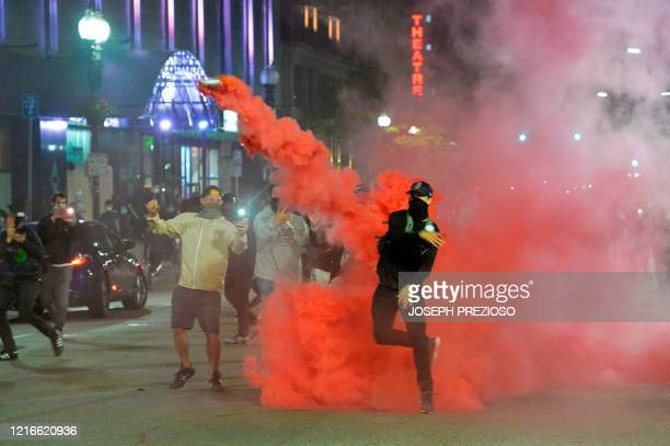 Protesters throw back smoke canisters during clashes with police during a demonstration over the death of George Floyd an unarmed black man who died...
