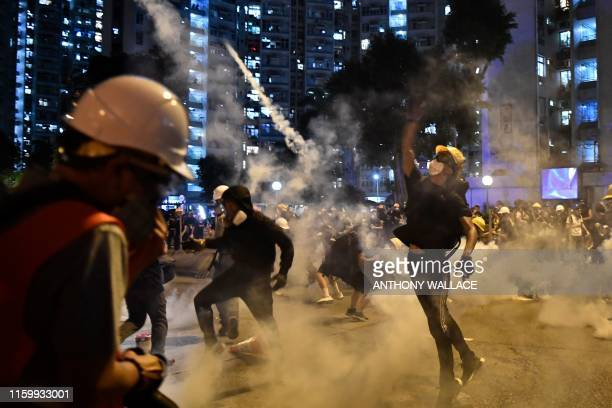 Protesters throw back tear gas fired by the police in Wong Tai Sin during a general strike in Hong Kong on August 5 as simultaneous rallies were held...