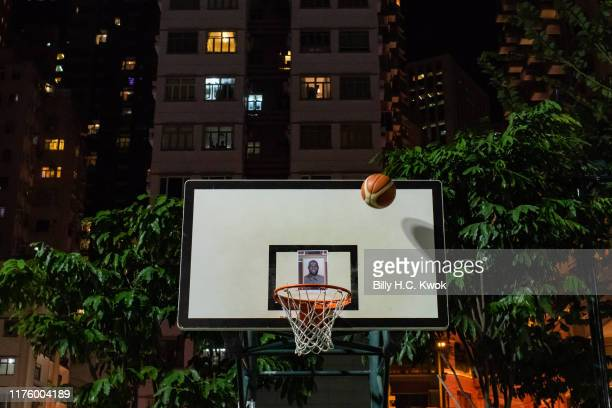 Protesters throw basketballs at a hoop with NBA star Lebron James' photo as they gather at the Southern Playground in support of NBA's Houston...