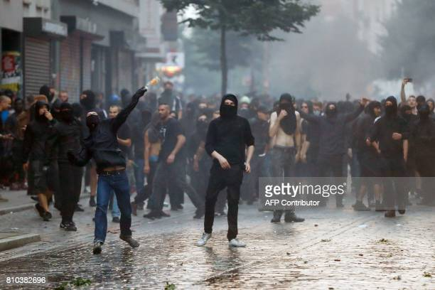 Protesters throw bottles at riot police on July 7 2017 in Hamburg northern Germany where leaders of the world's top economies gather for a G20 summit...