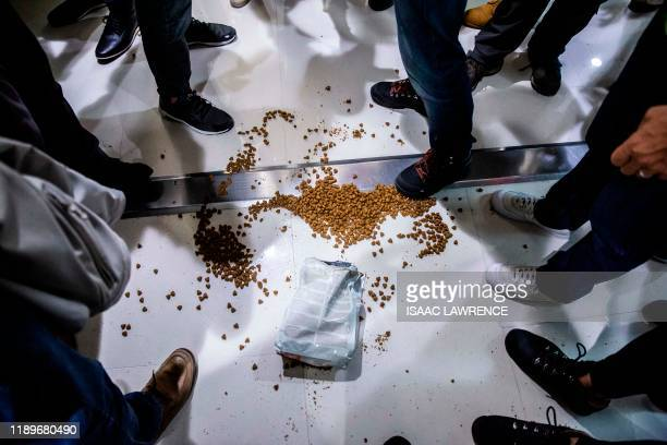 Protesters throw dog food on the ground near police during a march through the Harbour City shopping mall in the Tsim Sha Tsui district of Hong Kong...