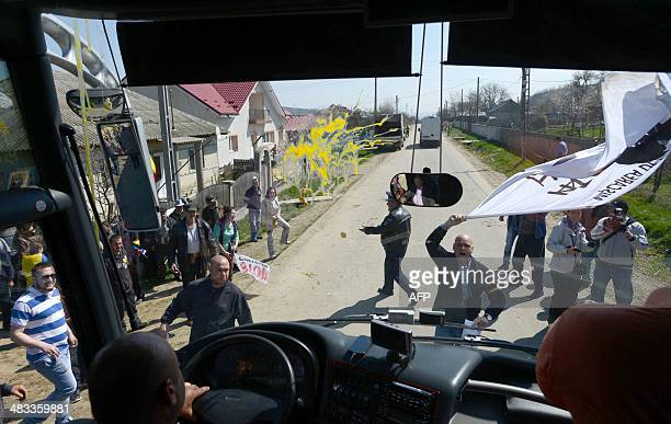 Protesters throw eggs against a bus carrying journalists who visited the exploration well started by US energy giant Chevron in the village of...