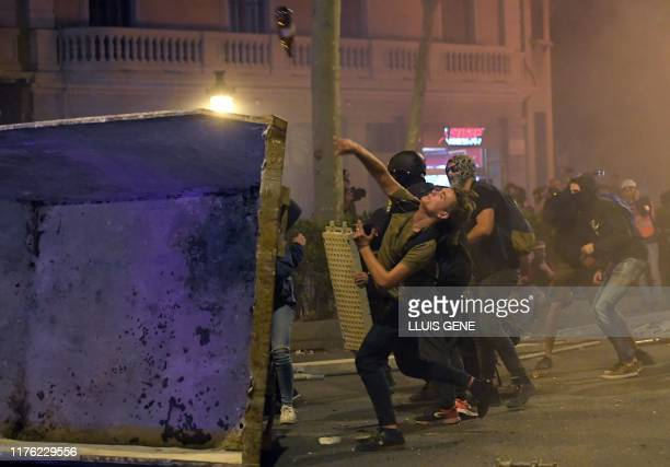 TOPSHOT Protesters throw objects against police during a demonstration called by the local Republic Defence Committees in Barcelona on October 16...