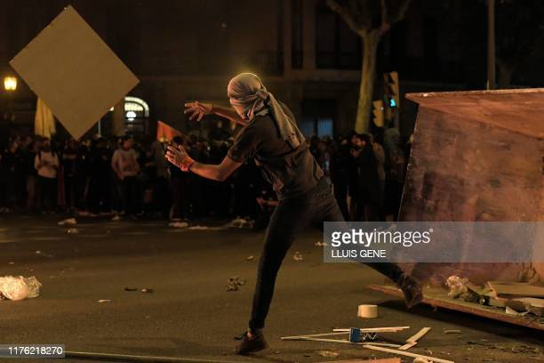 Protesters throw objects during a demonstration called by the local Republic Defence Committees in Barcelona on October 16 after police arrested 51...