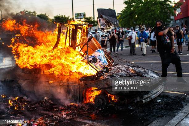 Protesters throw objects into a fire outside a Target store near the Third Police Precinct on May 28 2020 in Minneapolis Minnesota during a...