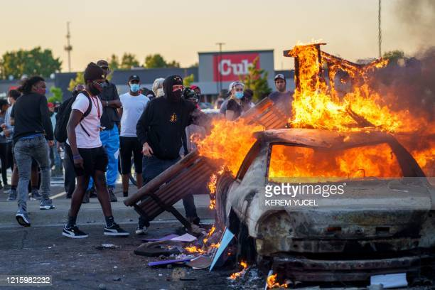 Protesters throw objects onto a burning car outside a Target store near the Third Police Precinct on May 28 2020 in Minneapolis Minnesota during a...