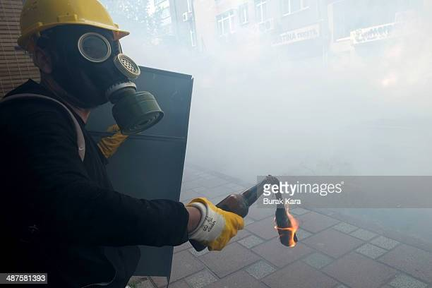 Protesters throw petrol bombs toward riot police during a May Day demonstration on May 1 2014 in Istanbul Turkey Turkish police fired water cannon...