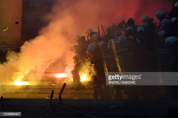 Protesters throw projectiles at riot police outside Serbia's National Assembly building in Belgrade on July 8 during a demonstration against a...