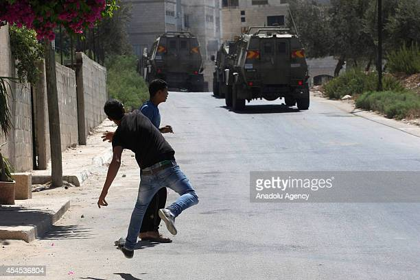 Protesters throw rocks at a convoy of Israeli military vehicles carrying out an incursion into the Ein Beit Elma refugee camp in the northern West...