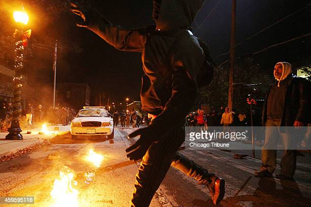 Protesters throw rocks at City Hall shortly before lighting a Ferguson Police Department squad car on fire on Tuesday Nov 25 in the wake of the grand...