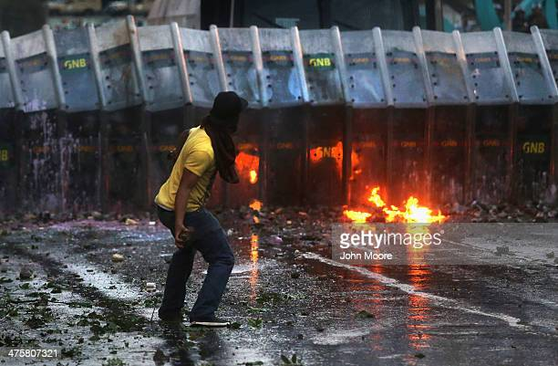 Protesters throw rocks at Venezuelan national guard troops during an antigovernment demonstration on February 27 2014 in Caracas Venezuela Almost...
