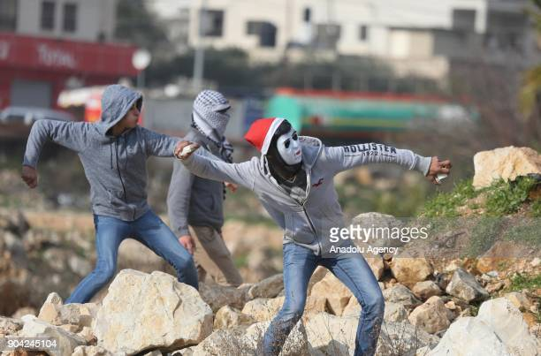Protesters throw rocks in response to Israeli security forces' intervention in a protest against US decision to recognize Jerusalem as Israel's...