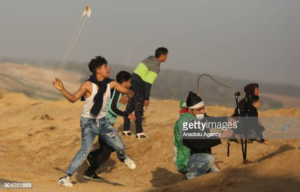 Protesters throw rocks in response to Israeli soldiers' intervention in a demonstration against US decision to recognize Jerusalem as Israel's...