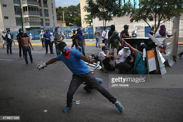 Protesters throw rocks while facing off against the Venezuelan national guard during an antigovernment demonstration on February 27 2014 in Caracas...
