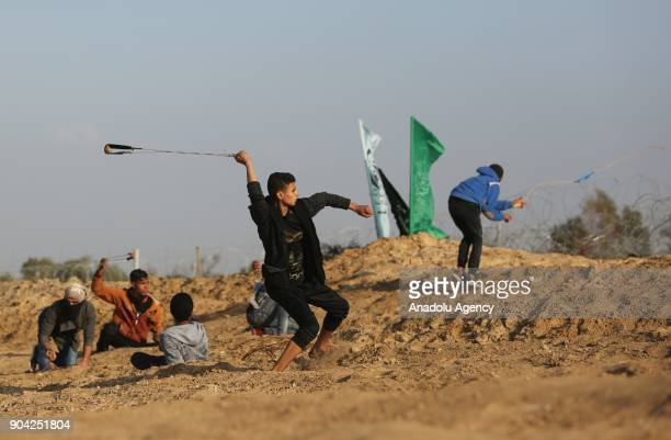 Protesters throw rocks with slingshots in response to Israeli soldiers' intervention in a demonstration against US decision to recognize Jerusalem as...