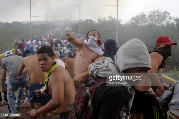 Protesters throw stones against the Venezuelan security forces as locals try to clear a path for humanitarian aid to enter Venezuela at Francisco de...