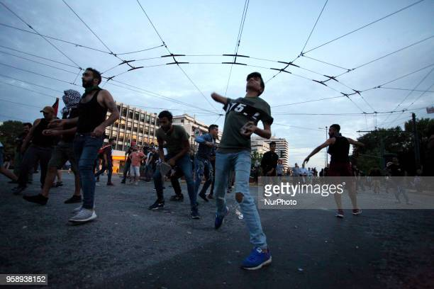 Protesters throw stones at the Israeli embassy during a protest rally by Palestinians outside the embassy of Israel in Athens Greece on May 15 2018...