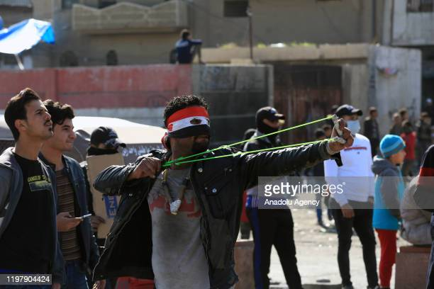 Protesters throw stones in response to security forces' intervention during an anti-government protest at Wathba Square in Iraqi capital Baghdad on...