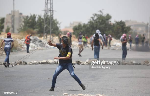 Protesters throw stones towards Israeli forces upon an intervention as students from Birzeit University gather at Bet Il Israeli military checkpoint...