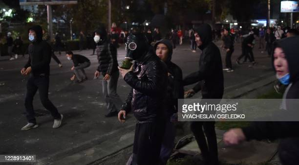 Protesters throw stones towards riot police during a rally against the results of a parliamentary vote in Bishkek on October 5, 2020.