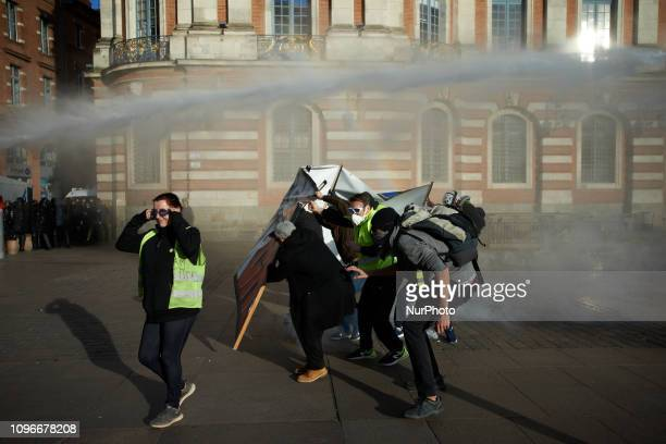 Protesters try to protect themselves from the water cannon behind a banner near the townhall of Toulouse the Capitole Act XIII dubbed 'Civil...