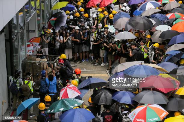 TOPSHOT Protesters try to push a metal cart through a closed entrance at the government headquarters in Hong Kong on July 1 2019 on the 22nd...