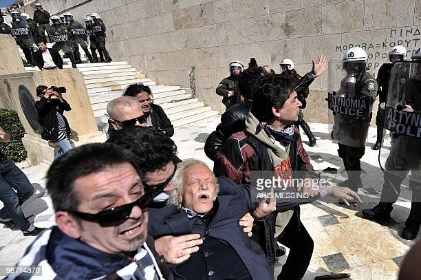Protesters try to save Manolis Glezos Greek left wing politician and writer known especially for his participation in the World War II resistance...