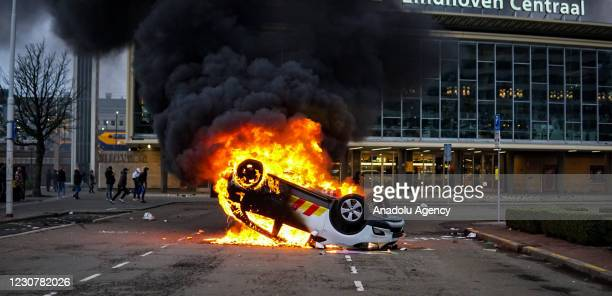 Protesters turn a car over and set ablaze during a protest against the coronavirus measures, near Eindhoven Central Station, in Eindhoven,...