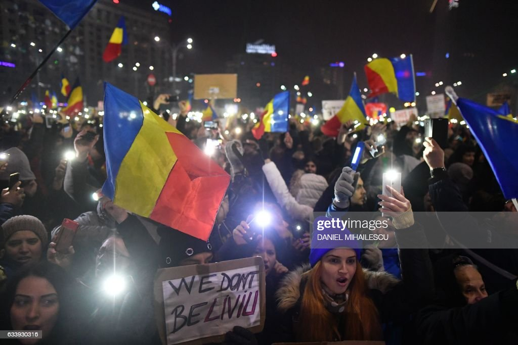 TOPSHOT - Protesters turn on the lights of their mobile phones as they protest in front of the government headquarters against the government's contentious corruption decree in Bucharest, Romania on February 5, 2017. 'WE DON'T BE-LIVIU (Dragnea)'. Romania's government formally repealed contentious corruption legislation that has sparked the biggest protests since the fall of dictator Nicolae Ceausescu in 1989, ministerial sources said. The emergency decree, announced on Tuesday (January 31, 2017), would have decriminalised certain corruption offences, raising concerns in Romania and outside that the government was easing up on fighting graft. Centre-right President Klaus Iohannis, elected in 2014 on an anti-graft platform, previously had called the decree 'scandalous' and moved to invoke the constitutional court. / AFP / Daniel MIHAILESCU
